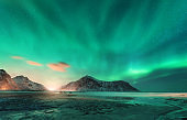 Aurora borealis above the snowy mountain and sandy beach in winter. Northern lights in Lofoten islands, Norway. Starry sky with polar lights. Night landscape with aurora, sea coast, city lights