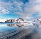 Snowy mountains and blue sky with clouds reflected in water in winter. Arctic sandy beach in Lofoten islands, Norway. Landscape with snow covered rocks, nordic sea coast, sand. Nature background