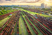 Aerial view of freight trains. Railway station. Rusty wagons on railroad. Heavy industry. Industrial landscape with train in depot, green trees, buildings, sky at sunset. Top view. Transportation