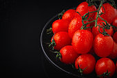 Fresh tomatoes on a plate on a black wooden table