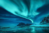 Aurora borealis over the snowy mountains and sandy beach in winter. Northern lights in Lofoten islands, Norway. Starry sky with polar lights. Night landscape with aurora, frozen sea coast, blue sky