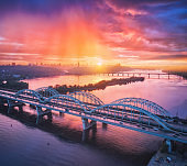 Aerial view of beautiful bridge at sunset in Kiev, Ukraine. Landscape with bridge, river, city, colorful sky with red clouds in summer. Cityscape with road, buildings, reflection in water. Top view