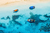 Aerial view of the fishing boats in clear blue water at sunny day in summer. Top view from drone of boat, yacht, sandy beach in Zanzibar. Travel. Tropical seascape with sailboats, sea. View from above