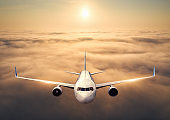 Airplane is flying above the clouds at sunset in summer. Landscape with passenger  airplane, low clouds, orange sky. Front view of aircraft. Business travel. Commercial plane. Aerial view. Take off