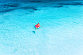 Aerial view of a young woman swimming with the pink donut swim ring in the clear blue sea at sunset in summer. Tropical aerial landscape with girl, clear azure water, sandy beach. Top view. Travel