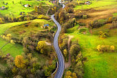 Aerial view of beautiful winding road in green hills at sunset in autumn. Colorful landscape with rural road, trees, grass and buildings in fall. Top view of curved roadway mountain village. Travel