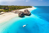 Aerial view of beautiful hotel on the water in ocean at sunset in summer. Zanzibar, Africa. Top view. Seascape with wooden hotel on the sea, boat, azure water, sandy beach, green palm trees. Resort