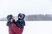 Father and Son Having Fun Outdoors During Snowstorm