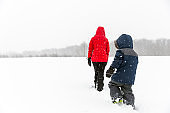 Mother and Son Walking in the Field in Winter During Snowstorm