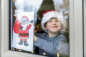 Young Boy sticking his Christmas drawing on home window during the Covid-19 Pandemic