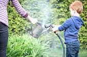 Cute Kid and Mother Gardening and Watering Garden While Quarantined at Home During Springtime