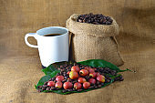 Coffee and fresh raw coffee beans with leaf on texture background