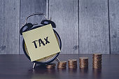 Tax word on yellow sticky note black alarm clock and stacked golden coin