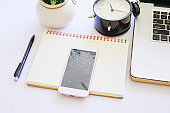 Top view of white office table with laptop, black alarm clock and crack smart phone on notebook