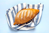 freshly baked sourdough bread on napkin from oven on blue wooden table Top view Flat lay Homemade pastry