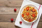 Fusilli - classic italian pasta from durum wheat with chicken meat, tomatoes cherry, basil in tomato sauce in white bowl on wooden table Mediterranean cuisine Top view Flat lay