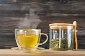 glass transparent cup of hot green tea with steam and can with tea leaves and spoon on wooden table Healthy drink, antistress beverage concept