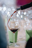 Red wine pouring into wine glass, close-up