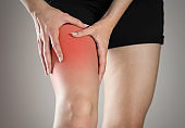 Pain in the leg of a woman. Highlighted in red. On a gray background. Close up