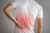 Lower back pain in a man. Highlighted in red. On a gray background. Close up