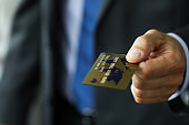 Man in suit and tie offering banking card to pay for service
