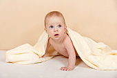 Happy newborn child relaxing after bath or showe on the bed at home