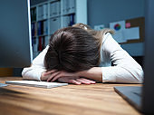 Tired female employee at office workplace taking nap