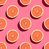 Seamless pattern of halves of grapefruit on pink background.