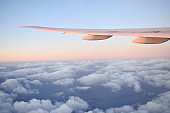 Aircarft wing above cloudscrap withbeautiful pink color of horizon in blue sky, view from airplane window.