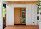 Covered porch and front door of beautiful new home. Features white siding and rich warm wood porch and ceiling. Door is closed.