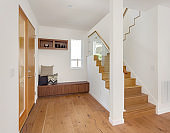 Bright and light entry in new home with front door, bench, and stairs with glass railing.