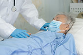 Doctor help Asian senior or elderly old lady woman patient wearing a face mask in hospital for protect safety infection and kill Novel Coronavirus (2019-nCoV) Covid-19 virus.