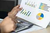 Asian accountant working and analyzing financial reports project accounting with chart graph and calculator in modern office : finance and business concept.