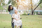 Help and care Asian senior or elderly old lady woman patient sitting on wheelchair at park in nursing hospital ward : healthy strong medical concept