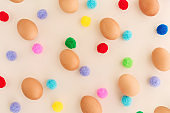 Easter eggs pattern with colorful pompoms on beige background.