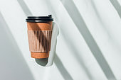 Craft paper coffee cup with hard shadows on white table.