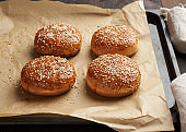 baked sesame buns on brown parchment paper, ingredient for a hamburger