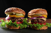 delicious burgers with fried beef cutlet, tomato, lettuce and onions, crispy white wheat flour bun with sesame seeds