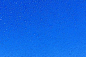 Close up of water drops on blue sky tone background. Abstract blue wet texture with bubbles on plastic PVC surface or grunge. Realistic pure water droplets condensed. Detail of canvas leather texture