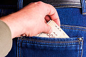 Stealing money from a pocket in the back. The thief pulls money out of the back pocket of his denim pants.