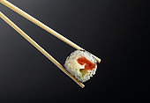 Fresh tasty sushi with wooden chopsticks on a dark background.