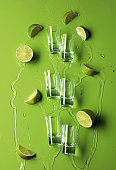 Small shot glasses with lime slices and flowing tequila on a green background.