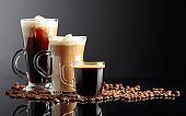 Espresso, latte macchiato and Irish coffee on black reflective background with coffee beans.