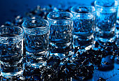 Damp glasses of vodka with ice on a black reflective background.