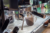 Coffee extraction from professional coffee machine. coffee machine preparing fresh coffee and pouring into cups at restaurant, bar or pub. Espresso shot from machine.