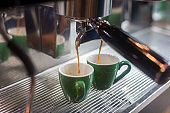 Coffee extraction from professional coffee machine . coffee machine preparing fresh coffee and pouring into cups at restaurant, bar or pub. Espresso shot from machine.