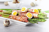 Asparagus wrapped in bacon with boiled quail eggs.