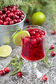 Glass of cranberry drink with berries, lime, and rosemary.