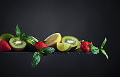 Fresh fruits and berries with mint on a black background.