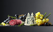 Blue cheese, dry-cured sausage, grapes, and rosemary on a black background.